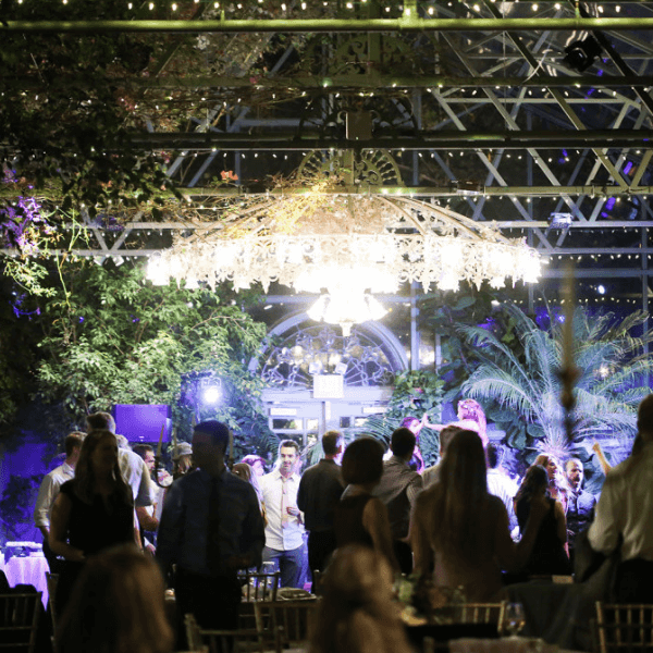 outdoor wedding reception in the utah mountains designed by AOO events with greenery and chandeliers.